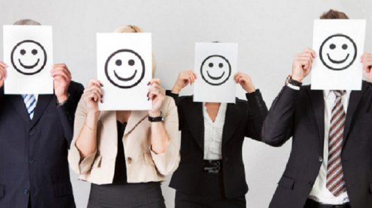 office workers holding smily faces in front of their faces