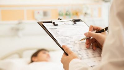 doctor filling in patient care form over hospital bed