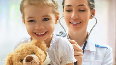 Healthcare sector nurse with stethoscope and child